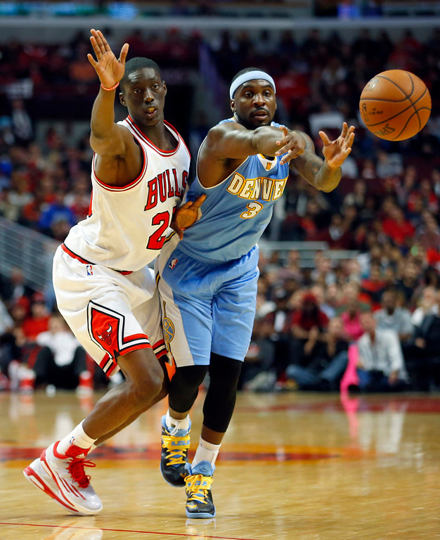 . Chicago Bulls forward Tony Snell (20) guards Denver Nuggets guard Ty Lawson (3) as Lawson makes a pass during the first half of a pre-season NBA basketball game in Chicago, on Monday Oct. 13, 2014. (AP Photo/Jeff Haynes)