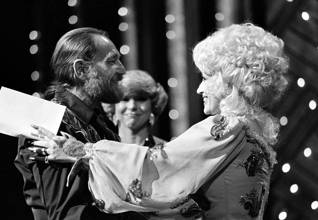 . Country music singer Willie Nelson, left, is congratulated by presenter and singer Dolly Parton as he receives the entertainer of the year award at the 13th annual Country Music Association awards show at Nashville\'s Grand Ole Opry House, Tenn., Oct. 9, 1979.  (AP Photo)