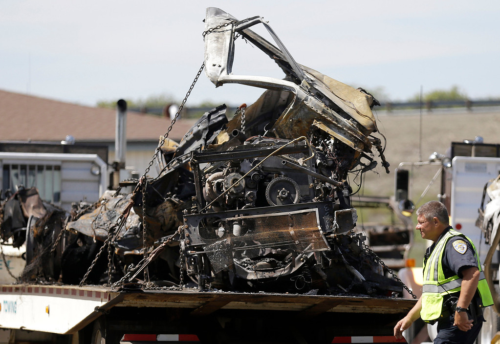 . A California Highway Patrol officer walks past the demolished cab of a FedEx truck  at a CalTrans maintenance station in Willows, Calif., Friday, April 11, 2014. At least ten people were killed and dozens injured in the fiery crash on Thursday, April 10, between a FedEx truck and a bus carrying high school students on a visit to a Northern California college. (AP Photo/Jeff Chiu)