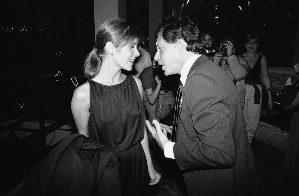 . As they enter the Underground disco in New York for a party for Henry Mancini, singer Eddie Fisher  chat, April 24, 1981. (AP Photo/Richard Drew)