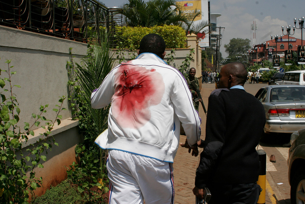 . A wounded man is escorted outside the Westgate Mall, an upscale shopping mall  in Nairobi, Kenya Saturday Sept. 21 2013, where shooting erupted when armed men attempted to rob a shop, according to police.  (AP Photo/Sayyid Azim)