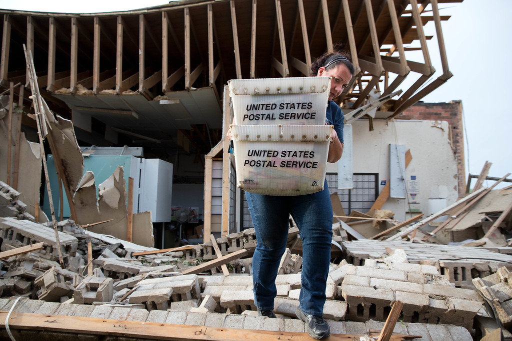 . Darcy Kleinschmit, left, a rural mail carrier from Norfolk, helps save the mail from the destroyed Pilger Post Office on Monday, June 16, 2014 in Pilger, Neb.  The National Weather Service says the storm that struck northeast Nebraska appears to have produced four tornadoes, one of which ravaged the town of Pilger.   (AP Photo/The World-Herald, Ryan Soderlin)