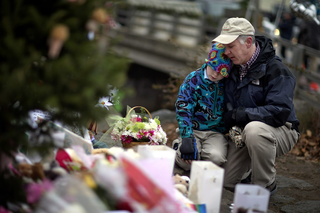 . David Freedman, right, kneels with his son Zachary, 9, both of Newtown, Conn., as they visit a sidewalk memorial for the Sandy Hook Elementary School shooting victims, Sunday, Dec. 16, 2012, in Newtown, Conn. A gunman walked into Sandy Hook Elementary School in Newtown Friday and opened fire, killing 26 people, including 20 children. (AP Photo/David Goldman)