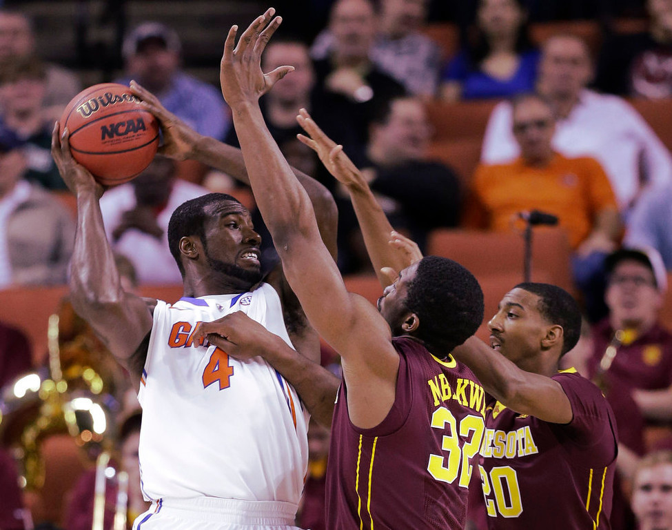 . Minnesota defenders Trevor Mbakwe (32) and Austin Hollins (20) pressure Florida\'s Patric Young (4) during the first half of a third-round game of the NCAA college basketball tournament Sunday, March 24, 2013, in Austin, Texas. (AP Photo/David J. Phillip)