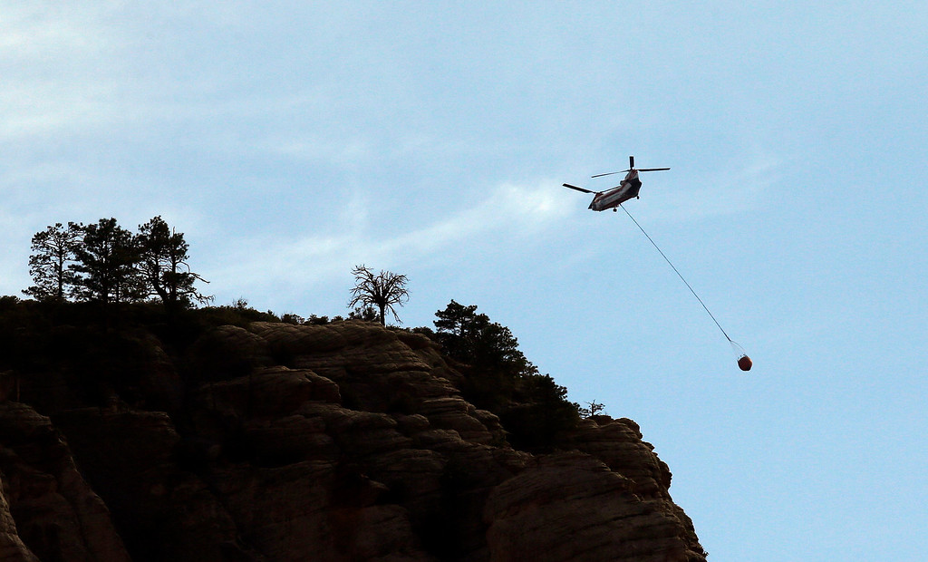 . A helicopter fighting the Slide Fire leaves the scene for a refill as the fire burns up Oak Creek Canyon on Thursday, May 22, 2014, in Sedona, Ariz.  The fire has burned approximately 4,800 acres. (AP Photo/Ross D. Franklin)
