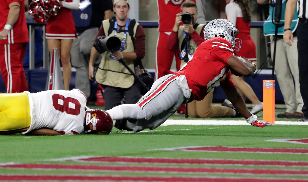 . Ohio State quarterback J.T. Barrett scores a touchdown against Southern California cornerback Iman Marshall (8) during the first half of the Cotton Bowl NCAA college football game in Arlington, Texas, Friday, Dec. 29, 2017. (AP Photo/LM Otero)