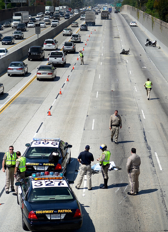 . California Highway Patrol officers and the Los Angeles County Coroner investigate a fatal motorcycle crash on the westbound 60 Freeway east of Hacienda Boulevard in Hacienda Heights Tuesday, March 26, 2013.(SGVN/Staff Photo by Sarah Reingewirtz)