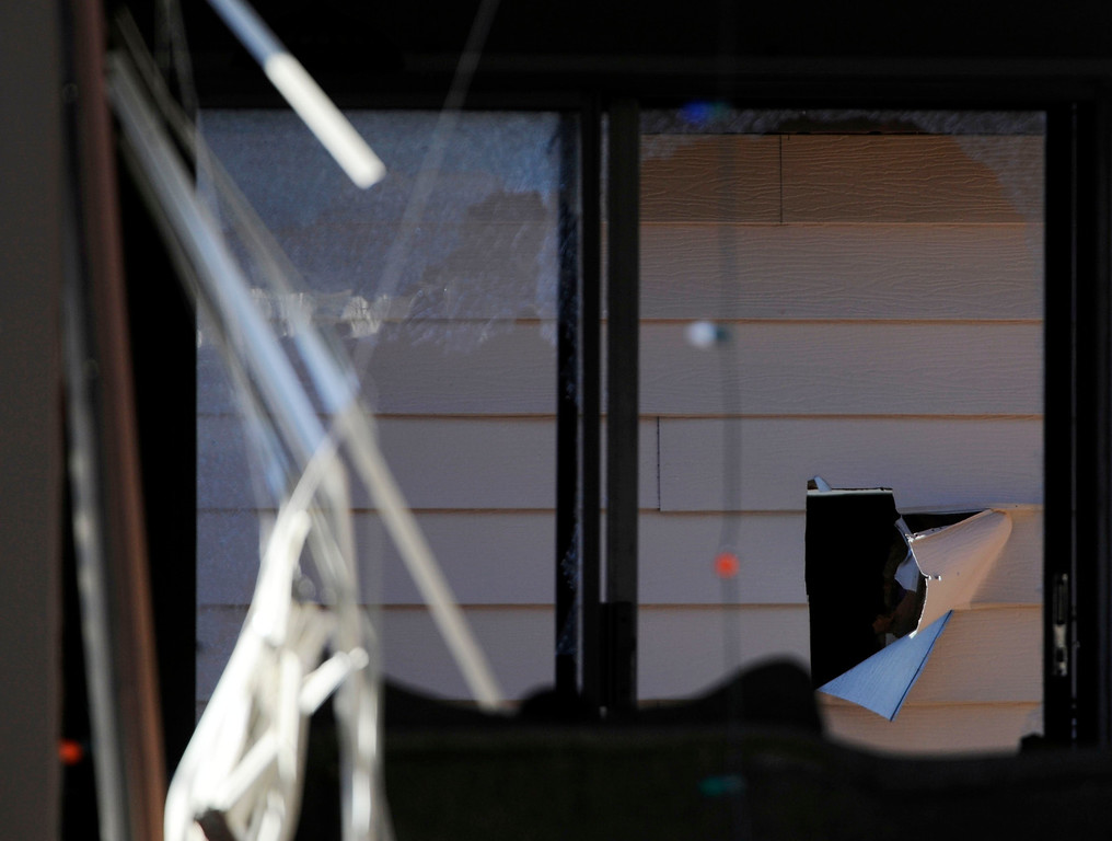 . A hole was torn into the wall in a garage behind the town home at 16005 Ithaca Place in Aurora Saturday afternoon. The bodies of four people, including a gunman are dead at the scene following a standoff situation early Saturday morning. The Denver Post/ Andy Cross