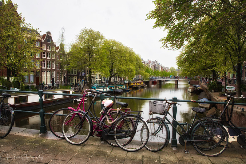 A canal in Amsterdam with the ever present row of bicycles  --- JohnBrody.com / John Brody Photography