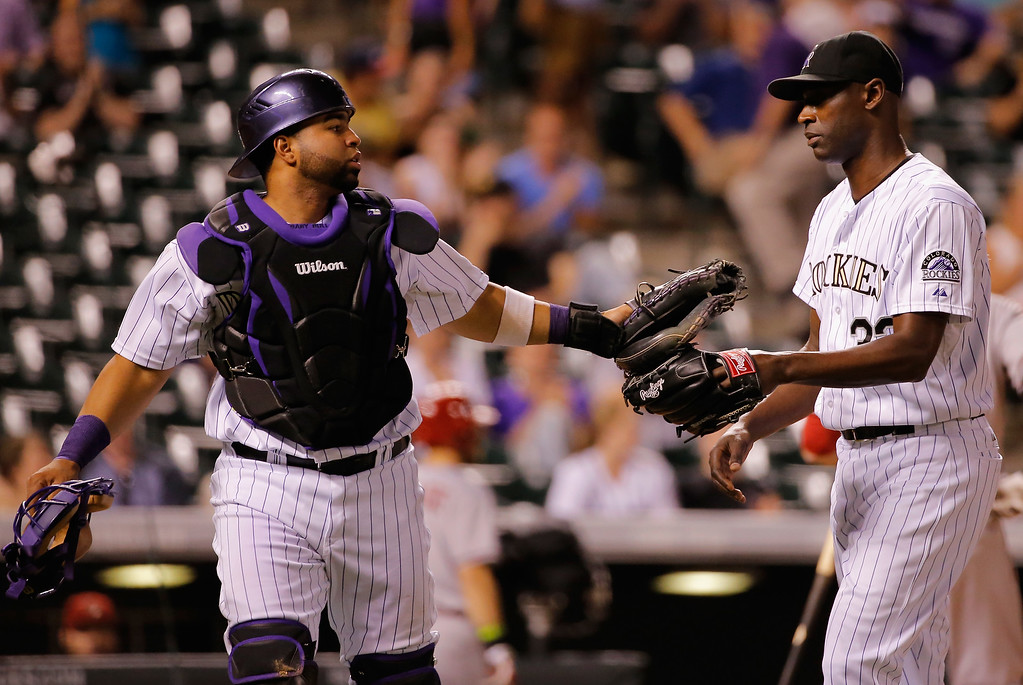 . DENVER, CO - SEPTEMBER 18:  Catcher Wilin Rosario #20 and closer LaTroy Hawkins #32 of the Colorado Rockies leave the field after Rosario caught a pop foul by Jake Lamb #19 of the Arizona Diamondbacks to end the top of the ninth inning at Coors Field on September 18, 2014 in Denver, Colorado. Hawkins went on to earn the win as Rosario hit a two run walk off home run as they Rockies defeated the Diamondbacks 7-6.  (Photo by Doug Pensinger/Getty Images)