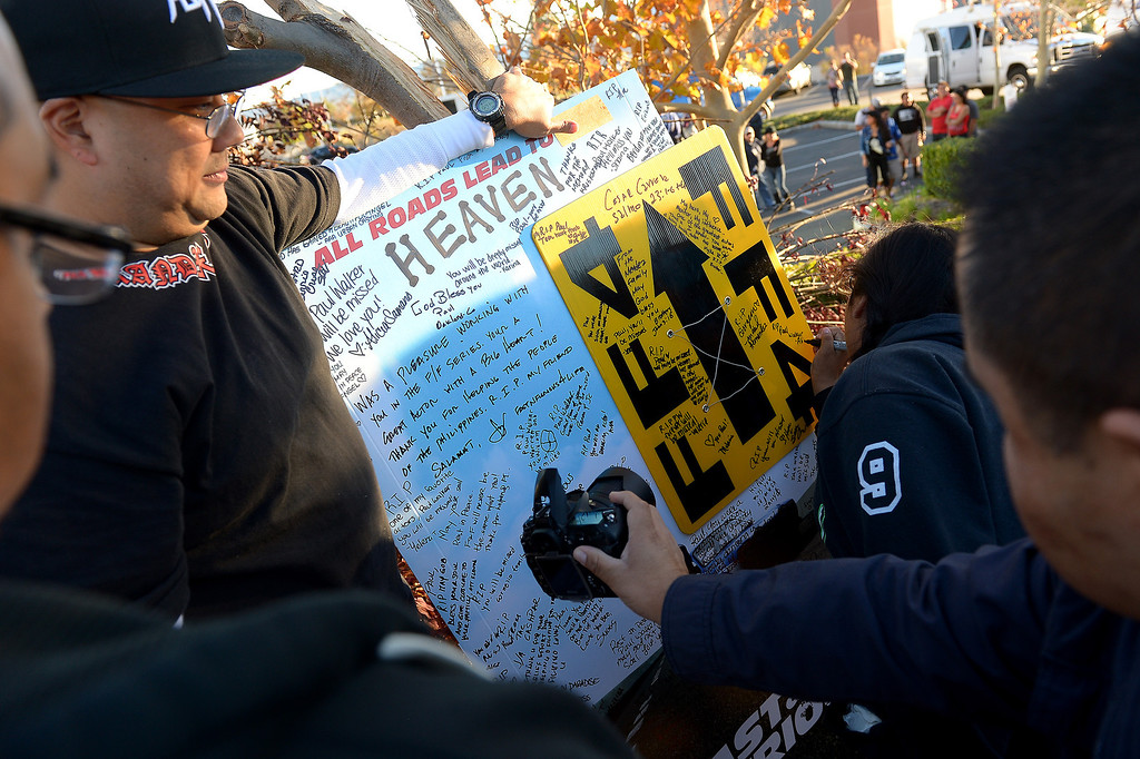 . People sign a memorial for Paul Walker and Roger Rodas, Sunday, December 1, 2013, at the scene of their fatal crash site on Hercules Street near Kelly Johnson Parkway in Valencia. (Photo by Michael Owen Baker/L.A. Daily News)