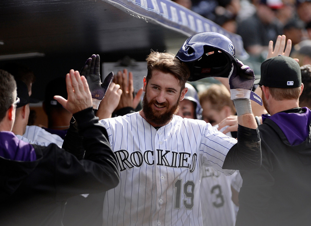 . Colorado Rockies outfielder, Charlie Blackmon, center, celebrates with his teammates after scoring on an RBI double hit by Carlo Gonzalez, in the 8th inning against the Chicago White Sox at Coors Field Wednesday afternoon, April 09, 2014. Michael Cuddyer also scored on the play. The Rockies went on to win 10-4. (Photo By Andy Cross / The Denver Post)