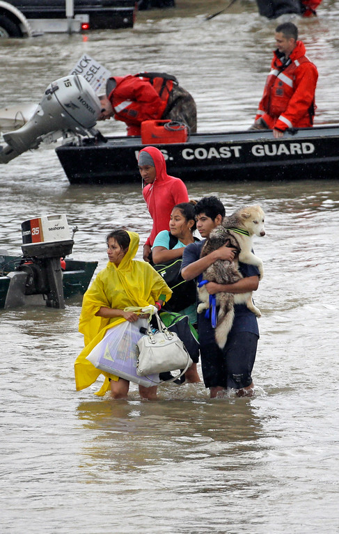 . Evacuees wade down Tidwell Rd. after being evacuated from their homes as floodwaters from Tropical Storm Harvey rise Monday, Aug. 28, 2017, in Houston. (AP Photo/David J. Phillip)