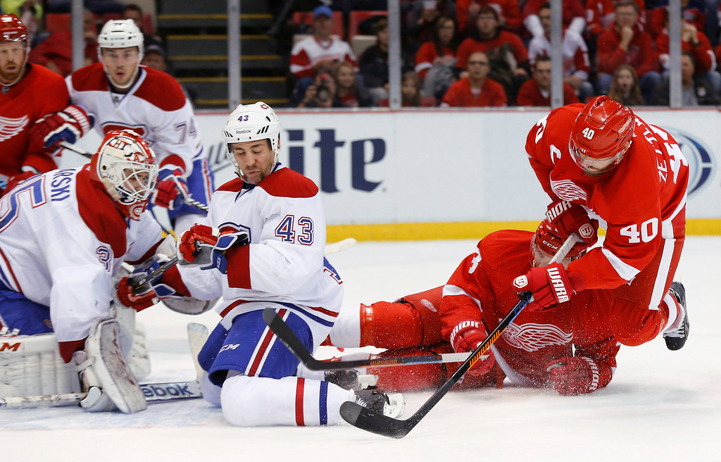 . Detroit Red Wings left wing Henrik Zetterberg (40) tries to shoot as he falls as Montreal Canadiens defenseman Mike Weaver (43) defends with goalie Dustin Tokarski (35) in the first period of an NHL hockey game in Detroit, Sunday, Nov. 16, 2014. (AP Photo/Paul Sancya)