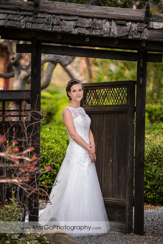 full body portrait of bride under wooden gate during bridal session at Shinn Historical Park and Arboretum in Fremont