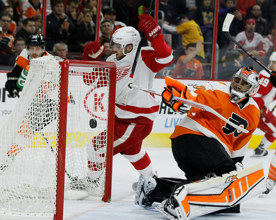 . Detroit Red Wings\' Riley Sheahan, center, raises his arms as he circles behind the net after scoring against the Philadelphia Flyers\' Ray Emery, right, in the first period of an NHL hockey game Saturday, Oct. 25, 2014, in Philadelphia. (AP Photo/Tom Mihalek)