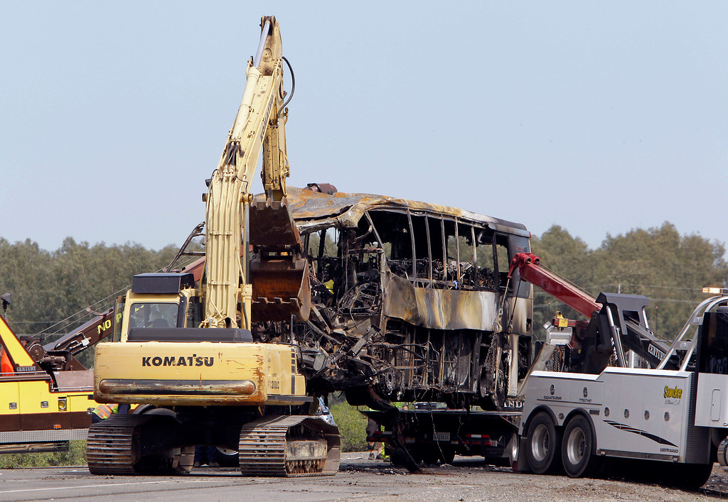 . As two two trucks lift, an excavator, helps push the remains of a tour bus onto the bed of a flatbed truck as it is removed from the scene of a multi-vehicle accident, Friday, April 11, 2014 in Orland, Calif.  At least people were killed and dozens injured in the fiery crash,Thursday, between a FedEx truck and a bus carrying high school students on a visit to a Northern California College.(AP Photo/Rich Pedroncelli)