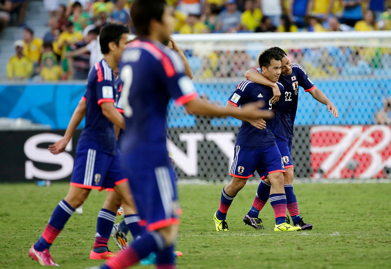 . Japan\'s Shinji Okazaki second from right, celebrates with teammate Japan\'s Maya Yoshida after scoring during the group C World Cup soccer match between Japan and Colombia at the Arena Pantanal in Cuiaba, Brazil, Tuesday, June 24, 2014. (AP Photo/Felipe Dana)