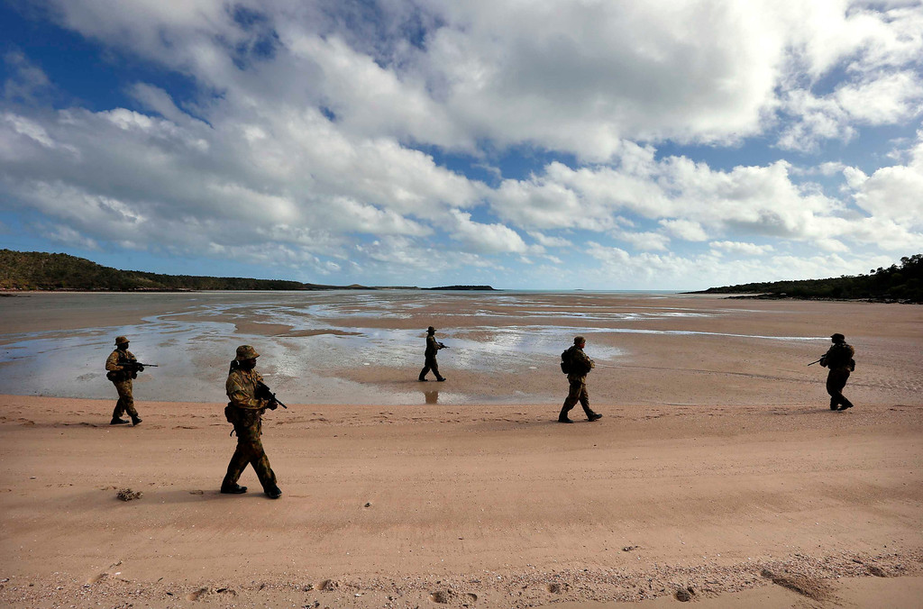 . Soldiers from Australia\'s North West Mobile Force (NORFORCE) unit walk in formation during a surveillance and reconnaissance patrol around Astell Island, part of the English Company Islands, located inside Arnhem Land in the Northern Territory July 17, 2013. NORFORCE is a surveillance unit that employs ancient Aboriginal skills to help in the seemingly impossible task of patrolling the country\'s vast northwest coast. NORFORCE\'s area of operations is about 1.8 million square km (700,000 square miles), covering the Northern Territory and the north of Western Australia. Aboriginal reservists make up a large proportion of the 600-strong unit, and bring to bear their knowledge of the land and the food it can provide. Fish, shellfish, turtle eggs and even insects supplement rations during the patrol, which is on the lookout for illegal foreign fishing vessels and drug smugglers, as well as people smugglers from  neighboring Indonesia. Picture taken July 17, 2013. REUTERS/David Gray