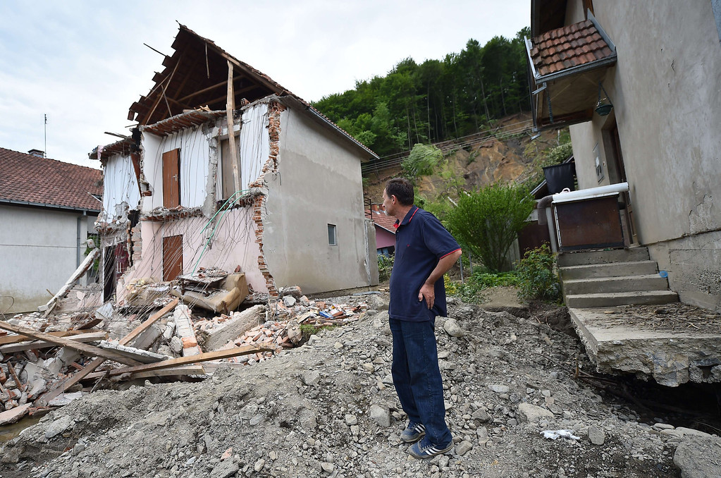 . A man stands near his house damaged by flooding and landslide in Krupanj, some 130 kilometers south west of Belgrade, on May 20, 2014, after the western Serbian town was hit with floods and landslides, cutting it off for four days. Serbia declared three days of national mourning on May 20 as the death toll from the worst flood to hit the Balkans in living memory rose and health officials warned of a possible epidemic.    AFP PHOTO / ANDREJ ISAKOVIC/AFP/Getty Images
