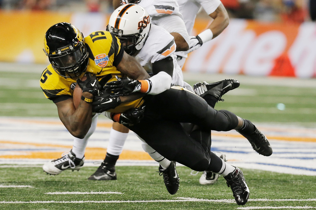 . Missouri wide receiver Dorial Green-Beckham (15) is tackled by Oklahoma State safety Daytawion Lowe (8) during the second half of the Cotton Bowl NCAA college football game on Friday, Jan. 3, 2014, in Arlington, Texas. (AP Photo/Brandon Wade)