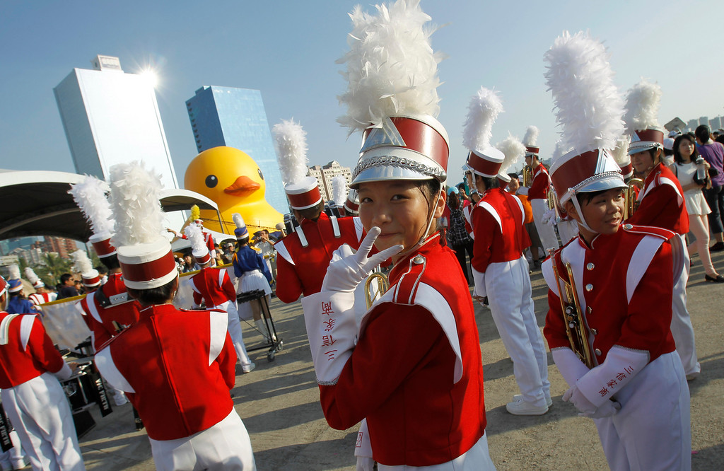 . A member of a school marching band jokes around while she waits to perform for the arrival of a giant yellow duck at the port of Kaohsiung, Taiwan, Thursday, Sept. 19, 2013.   (AP Photo/Wally Santana)