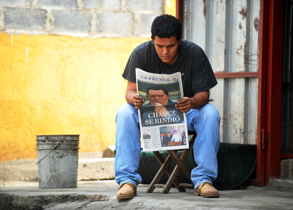 . A young man reads a local newspaper the day after the death of Venezuelan President Hugo Chavez, on March 6, 2013, in Managua, Nicaragua. Venezuela was plunged into uncertainty Wednesday after the death on the eve of President Hugo Chavez, who dominated the oil-rich country for 14 years and came to embody a resurgent Latin American left. AFP PHOTO/Hector  RETAMAL/AFP/Getty Images