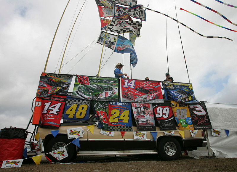 """. Jim \'The Jackman\"""", center, stands on top of his van covered with NASCAR banners and flags as he watches drivers practice laps Thursday, Feb. 12, 2009 at Daytona International Speedway in Daytona Beach, Fla.(AP Photo/J Pat Carter)"""