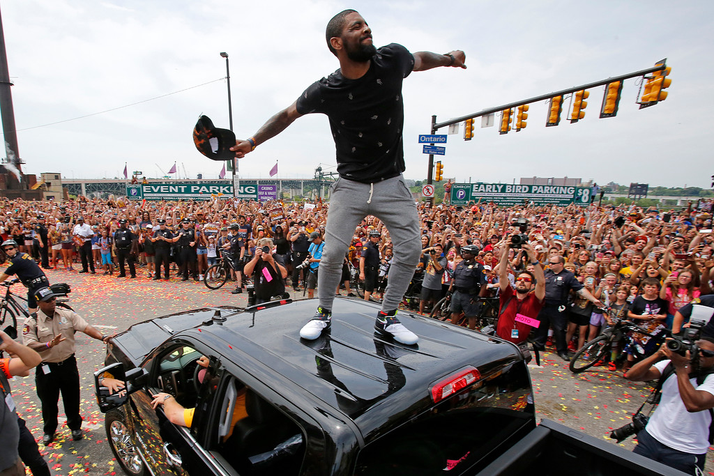 . Cleveland Cavaliers\' Kyrie Irving tosses his ball cap into the crowd from the roof of a pickup truck before the start of a parade celebrating the Cleveland Cavaliers\' NBA Championship in downtown Cleveland Wednesday, June 22, 2016. (AP Photo/Gene J. Puskar)