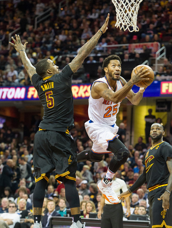. New York Knicks\' Derrick Rose (25) drives past Cleveland Cavaliers\' J.R. Smith (5) as the Cavaliers LeBron James watches during the first half of an NBA basketball game in Cleveland, Tuesday, Oct. 25, 2016. (AP Photo/Phil Long)