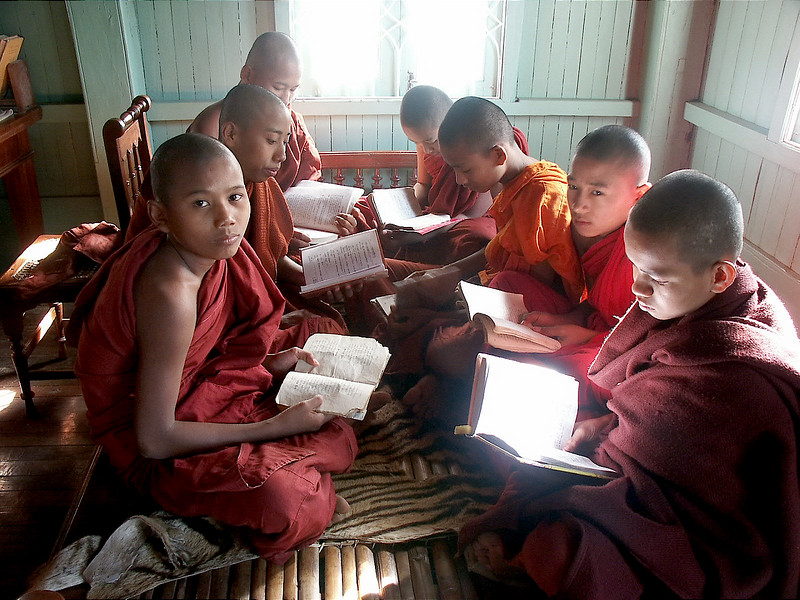 Young monkes in a Myanmar village, study their texts on a tiger skin.