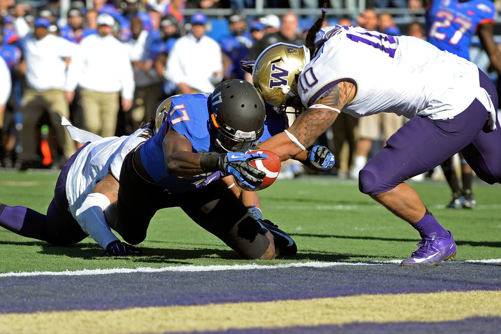 Description of . Boise State's Geraldo Boldewijn (17) reaches over the goal line to score  a touchdown despite pressure from Washington's John Timu (10) during the first half of the MAACO Bowl NCAA college football game on Saturday, Dec. 22, 2012, in Las Vegas. (AP Photo/David Becker)