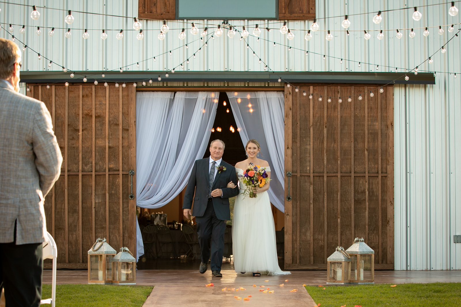 bride starting her walk down the aisle with her father string lights overhead and rustic lanterns on the ground