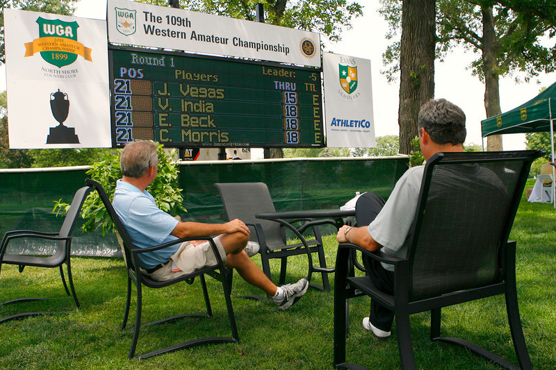 Viewers sit by the leader board during the first round Tuesday.