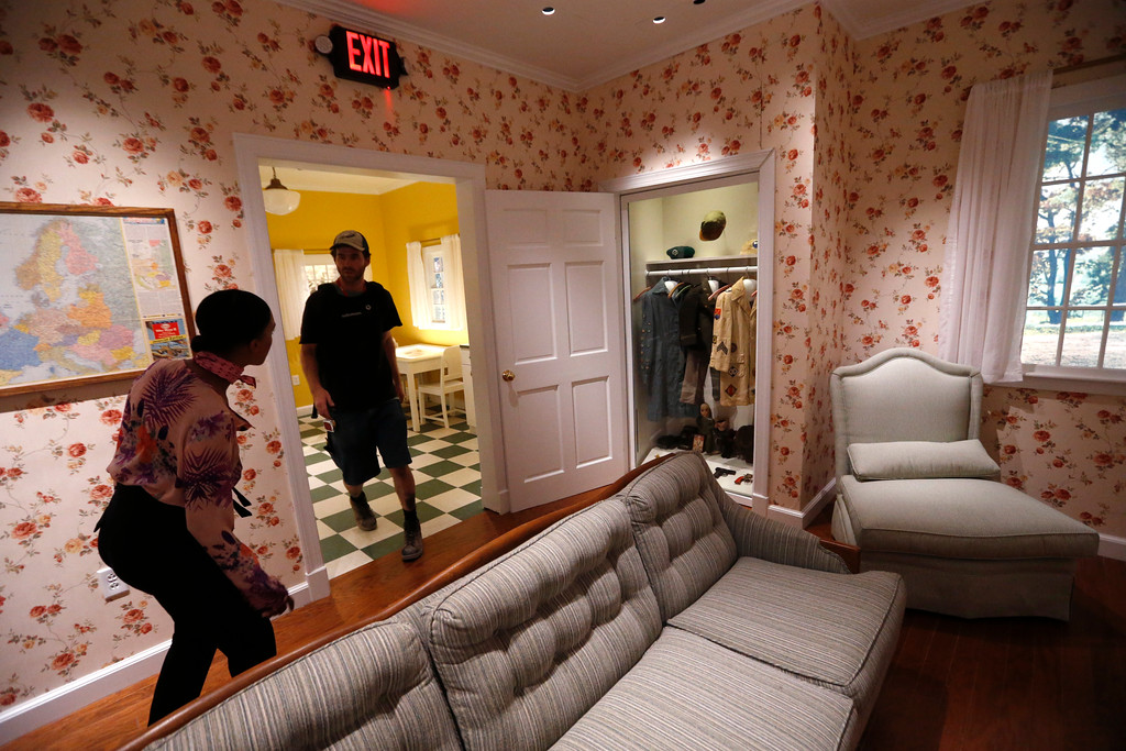 ". Employees walk through a mock-up of a 1940s-style living room, with military uniforms hanging in the closet, as part of the permanent exhibit ""Salute to the Home Front\"" at the National World War II Museum, which will open to the public this Saturday, in New Orleans, Monday, June 5, 2017. The exhibit tells the home front story from the 1920s to the development of the atomic bomb. (AP Photo/Gerald Herbert)"
