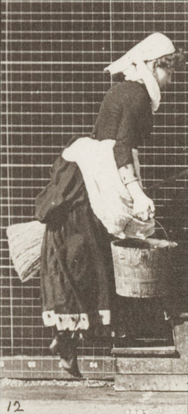 Woman turning to ascend stairs with a bucket of water and broom in hands