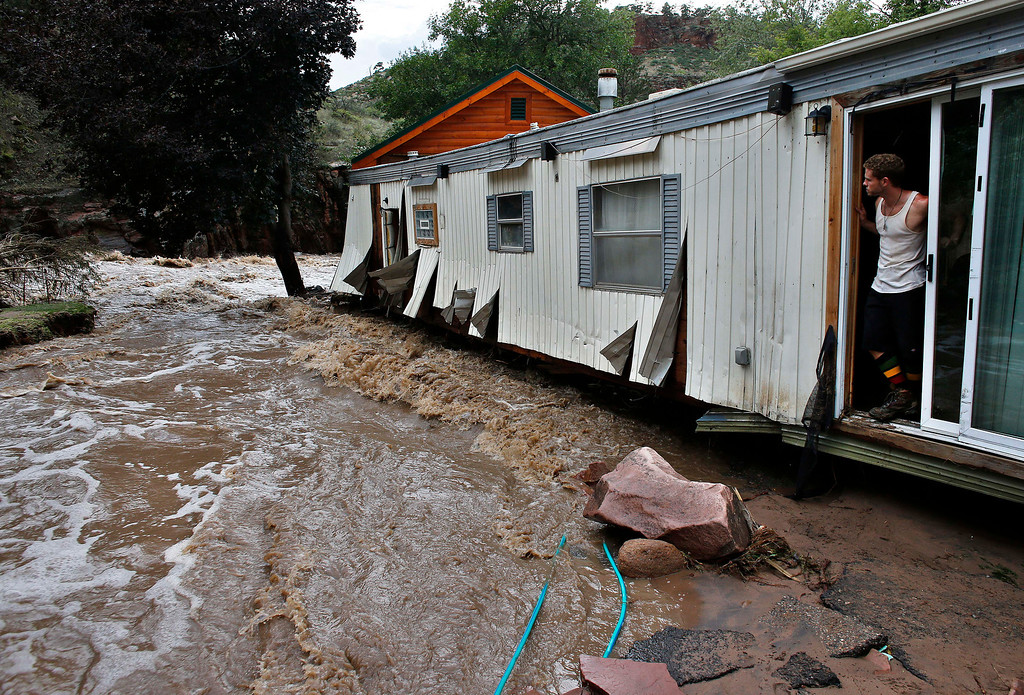 . Local resident Chris Rodes takes a break while helping salvage a friend\'s belongings after floods left homes and infrastructure in a shambles, in Lyons, Colo., Friday Sept. 13, 2013.  (AP Photo/Brennan Linsley)