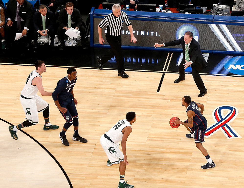 . Michigan State head coach Tom Izzo, top right, talks to his team during the first half in a regional semifinal at the NCAA college basketball tournament against Connecticut, Sunday, March 30, 2014, in New York. (AP Photo/Julio Cortez)