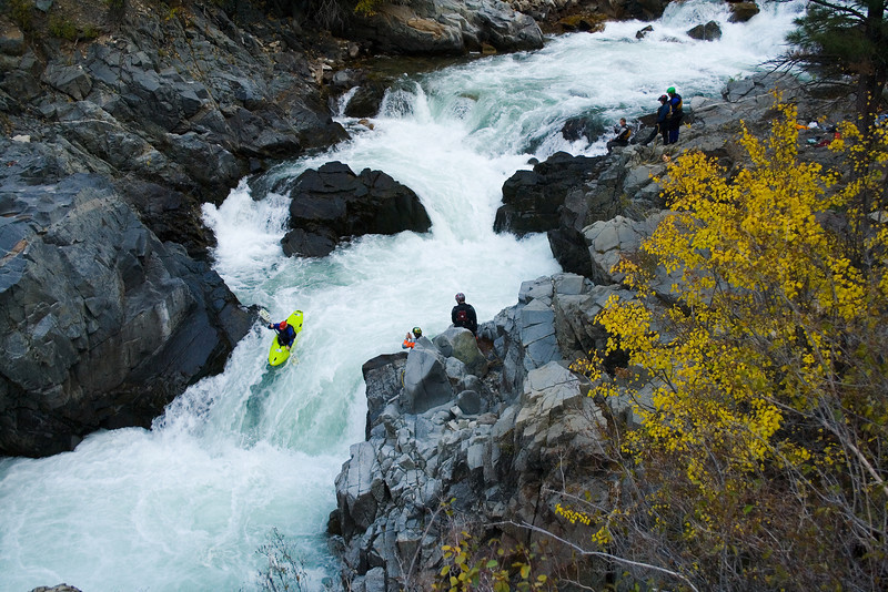 Paddler Preston Woods on the last drop of Big Falls as friends watch and set safety. South Fork Payette River-Canyon section in Idaho.