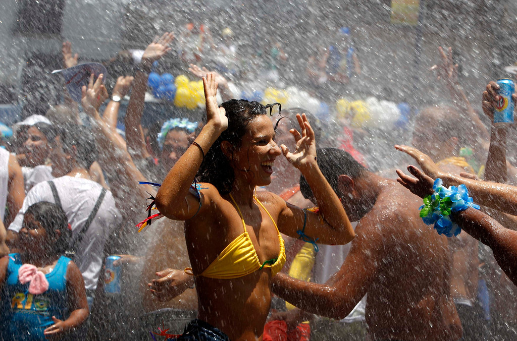 ". Water is sprinkled on revellers to help them cool off during an annual block party known as ""Escravos da Maua\"", one of the many carnival parties to take place in the neighborhoods of Rio de Janeiro February 3, 2013. REUTERS/Pilar Olivares"