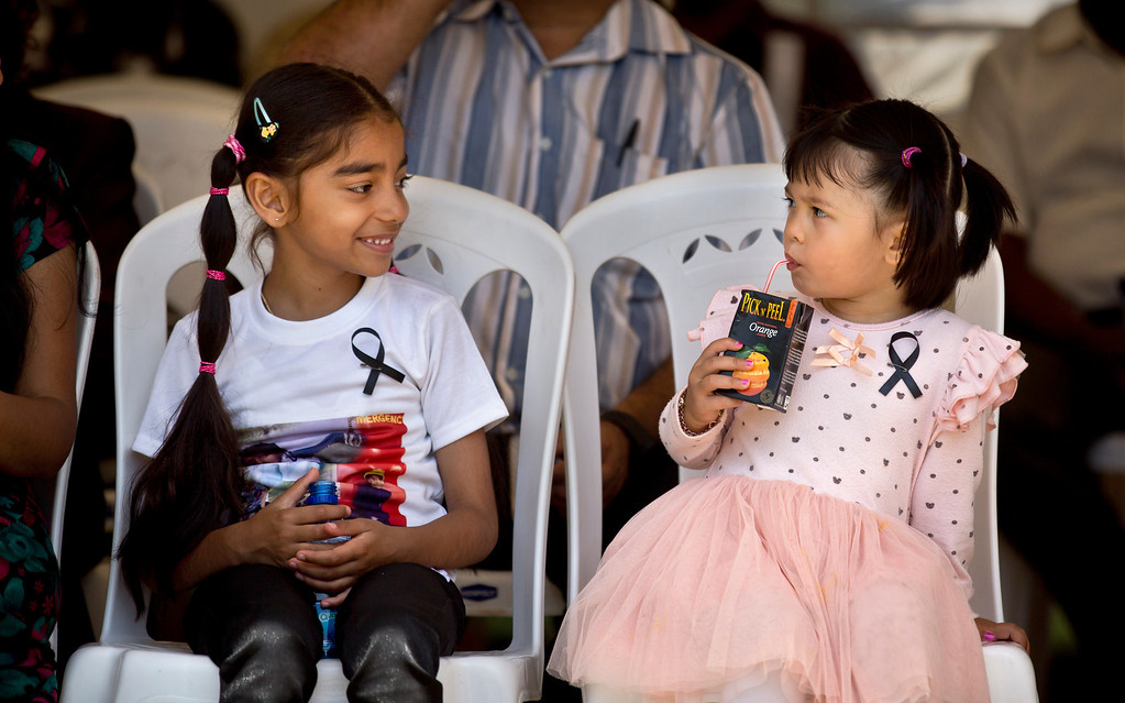 . Stella, 3, right, whose mother Wendy Zhang lost her sister-in-law Zhou Jian in the Westgate attack, and an unidentified child relative of one of the victims, left, wear black ribbons as they attend a memorial service marking the one-month anniversary of the Sept. 21 Westgate Mall terrorist attack, in Karura Forest in Nairobi, Kenya Monday, Oct. 21, 2013. (AP Photo/Ben Curtis)