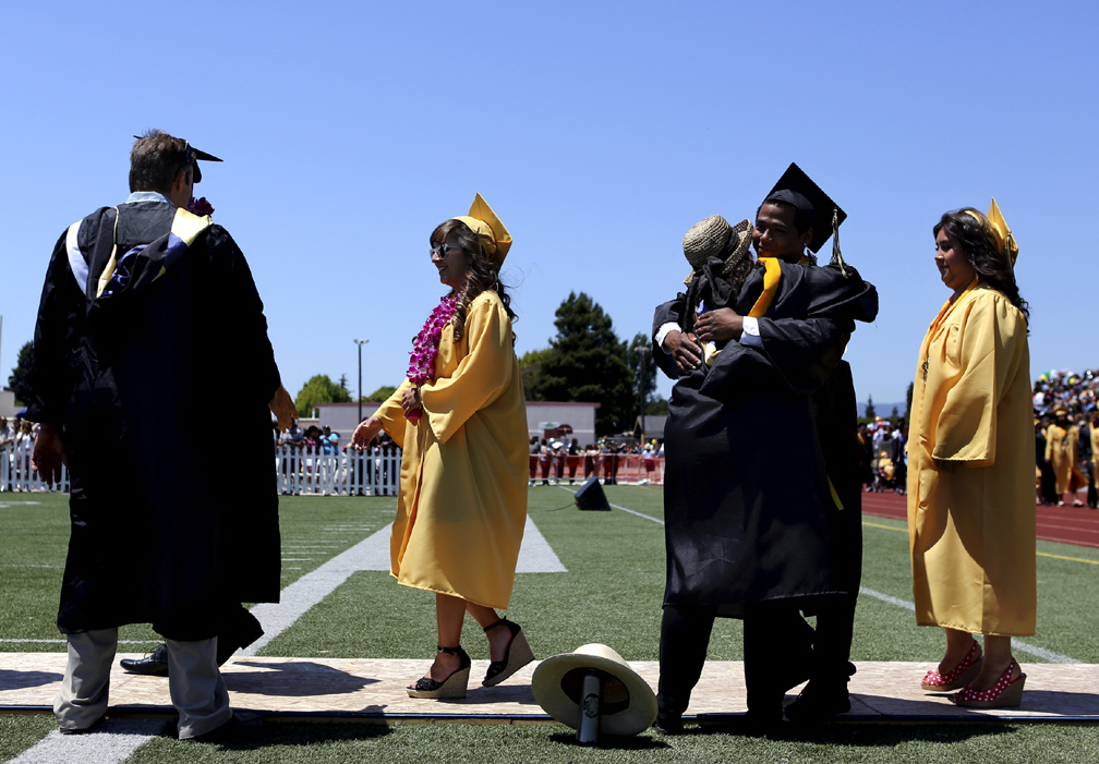 . Graduates embrace Watsonville High teachers and staff as they walk onto the school\'s football field during the 2013 graduation ceremony on Friday. (Kevin Johnson/Sentinel)