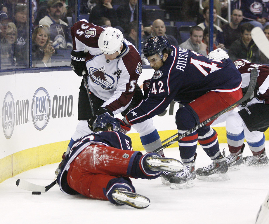 . Columbus Blue Jackets\' Artem Anisimov (42), of Russia, battles for the puck with Colorado Avalanche\'s Cody McLeod (55) during the first period of an NHL hockey game, Tuesday, April 1, 2014, in Columbus, Ohio. Columbus\' David Savard (58) is on the ice. (AP Photo/Mike Munden)