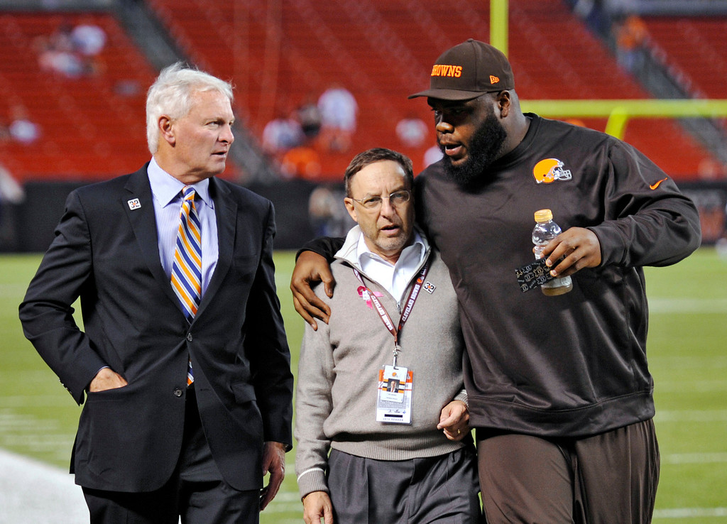 . Cleveland Browns nose tackle Phillip Taylor, right, hugs team CEO Joe Banner as they walk with team owner Jimmy Haslam, left, before an NFL football game against the Buffalo Bills on Thursday, Oct. 3, 2013, in Cleveland. (AP Photo/David Richard)