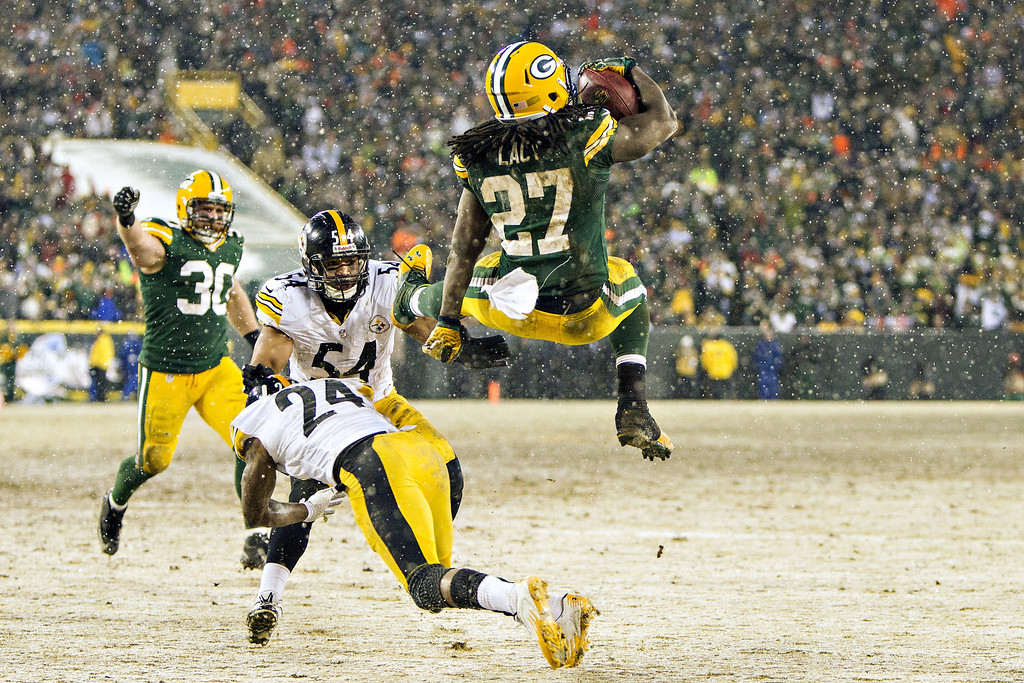 . Eddie Lacy #27 of the Green Bay Packers dives through the air into the end zone for a touchdown against the Pittsburgh Steelers at Lambeau Field on December 22, 2013 in Green Bay, Wisconsin.  (Photo by Wesley Hitt/Getty Images)