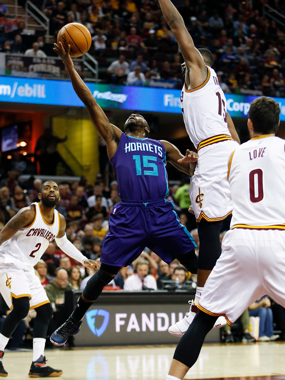 . Charlotte Hornets\' Kemba Walker (15) goes up for a shot against Cleveland Cavaliers\' Tristan Thompson (13), Kevin Love (0) and Kyrie Irving (2) during the second half of an NBA basketball game, Sunday, Nov. 13, 2016, in Cleveland. The Cavaliers won 100-93. (AP Photo/Ron Schwane)