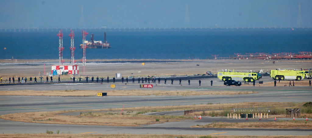 . A line of people begin to comb a runway where an Asiana Airlines jet crashed on landing at San Francisco International Airport Saturday afternoon, July 6, 2013.  (Karl Mondon/Bay Area News Group)