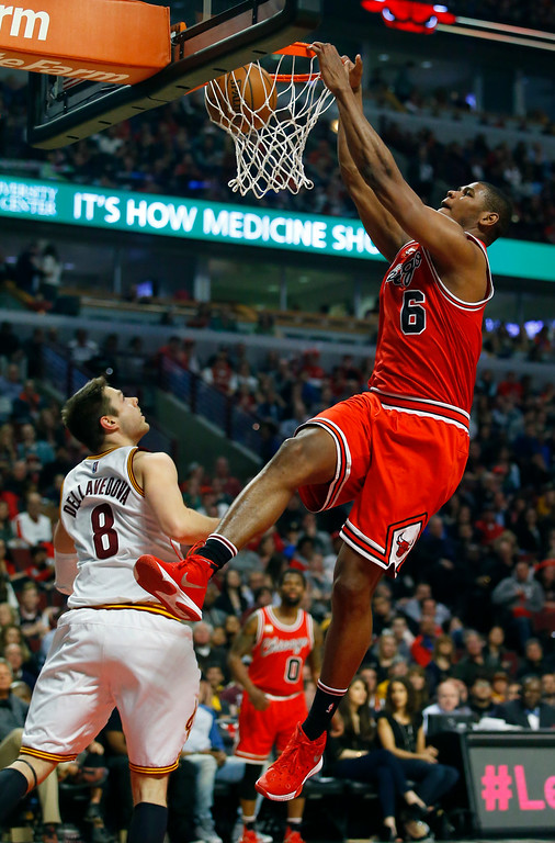 . Chicago Bulls forward Cristiano Felicio (6) dunks over Cleveland Cavaliers guard Matthew Dellavedova (8) during the second half of an NBA basketball game in Chicago on Saturday, April 9, 2016. (AP Photo/Jeff Haynes)