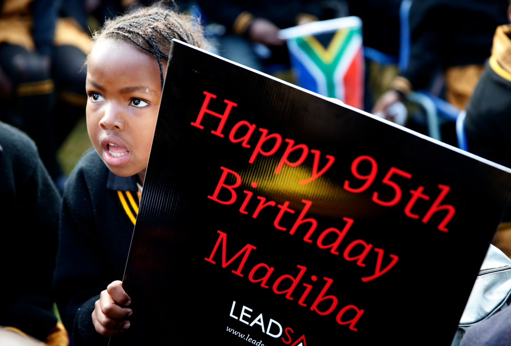 """. Children hold placards as they gather to wish to former President Nelson Mandela happy birthday at a township school in Atteridgeville near Pretoria, July 18, 2013. Anti-apartheid hero Mandela is \""""steadily improving\"""", South Africa\'s government said on Thursday as the former president celebrated his 95th birthday in hospital amid tributes from around the country and the world. REUTERS/Mike Hutchings"""