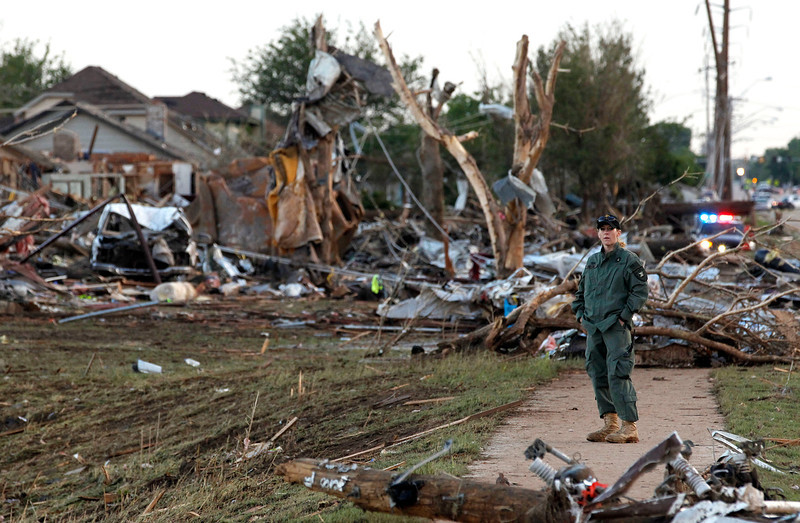 . A member of a security team helps guard an area of rubble from a destroyed residential neighborhood, one day after a tornado moved through Moore, Okla., Tuesday, May 21, 2013. The huge tornado roared through the Oklahoma City suburb Monday, flattening entire neighborhoods and destroying an elementary school with a direct blow as children and teachers huddled against the winds. (AP Photo/Brennan Linsley)